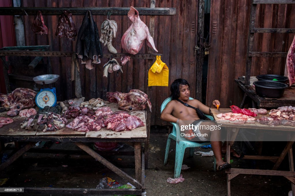 A meat vendor waits for customers at the Saturday markets on April 19, 2014 in Palo, Leyte, Philippines. People continue to rebuild their lives five months after Typhoon Haiyan struck the coast on November 8, 2013, leaving more than 6000 dead and many more homeless. Although many businesses and services are functioning, electricity and housing continue to be the main issues, with many residents still living in temporary housing conditions due to 'No Build' areas preventing them from rebuilding their homes. This week marks Holy Week across the Philippines and will see many people attending religious activities.