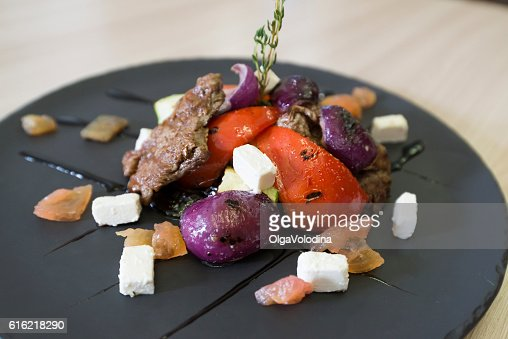 Meat with vegetables and cheese in restaurant : Bildbanksbilder
