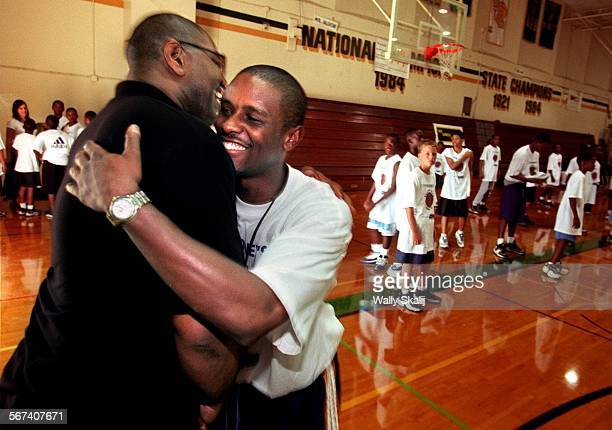 MEBasketball20813WS––Boston Celtic and former Long Beach Poly star Tyus Edny right hugs former coach Ray Porter during a basketball camp Thursday...