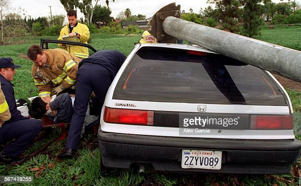 MEcarcrash0103AAG––kodak––Fountain Valley firefighters and paramedics attend to the driver of a Honda Civic who was injured after his car crashed...