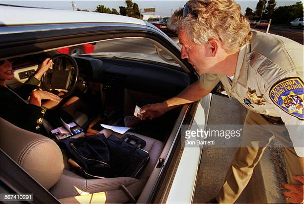 MECarpoolFreyDB102198––FountainValley–– California Highway Patrol officer Andre Frey inspects license of a motorist he pulled over for driving alone...