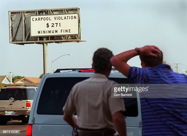 MECarpoolSignDB102198––FountainValley–– California Highway Patrol officer Andre Frey listens to a motorist explain why he was driving solo in the...