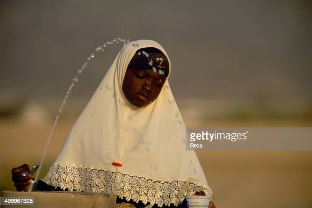 2000 Mecca Saudi Arabia A young veiled woman serves herself some water from a fountain during the pilgrimage of the Haj For Muslims the Haj is the...