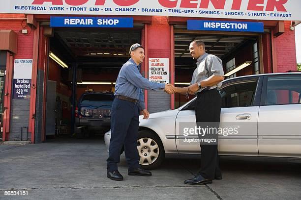 Mechanic and customer shaking hands