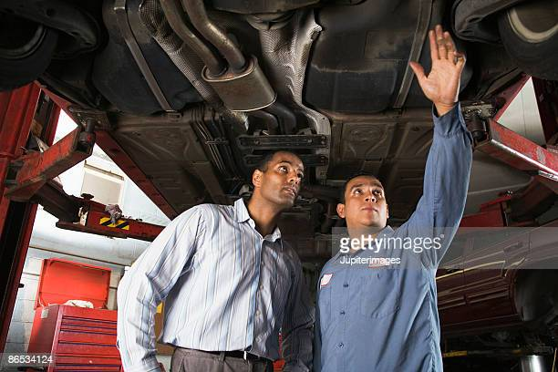 Mechanic and customer underneath car
