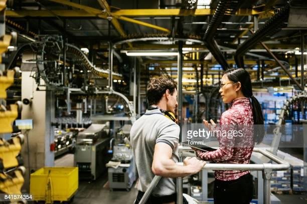 Mecánico e ingeniero mujer hablando en fábrica