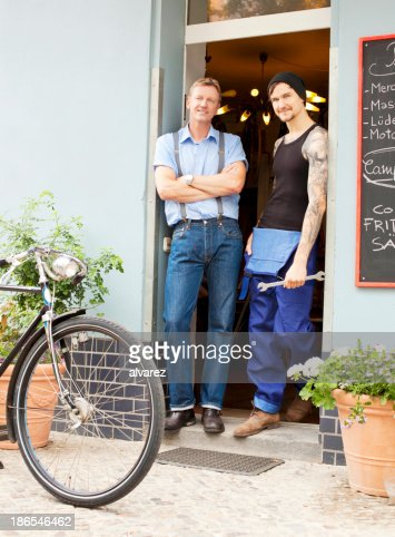 Mechanic and owner in front of their bike shop : Stock Photo