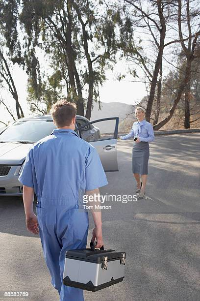 Mechanic arriving to help stranded woman