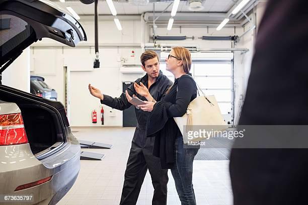 Mechanic assisting female customer in using mobile app at auto repair shop