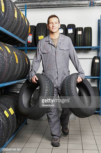 Mechanic carrying tyre in each hand, smiling, portrait