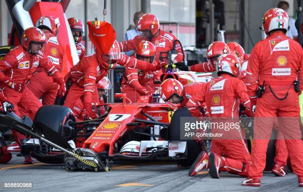 Mechanic change tires for Ferrari's Finnish driver Kimi Raikkonen at the pit during the Formula One Japanese Grand Prix at Suzuka on October 8 2017 /...