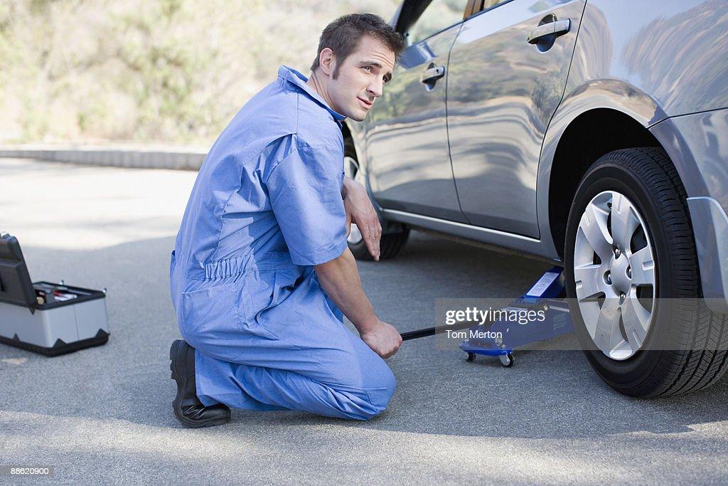 Mechanic changing cars flat tire : Stock Photo