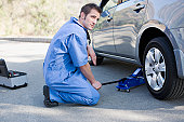 Mechanic changing cars flat tire