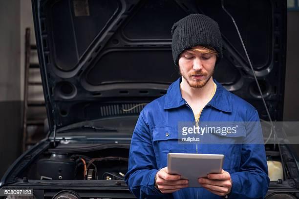 Mechaniker, die eine Auto-Motor mit digitalen tablet