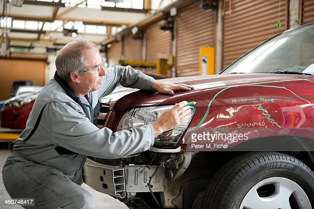 Mechanic checking damaged automobile