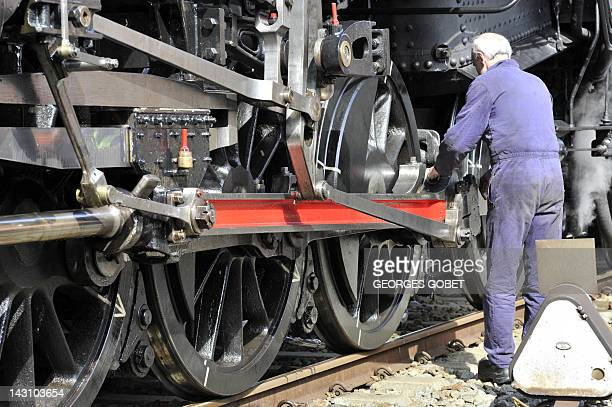 A mechanic checks a Belgian 1940s locomotive on April 18 2012 at The Gare du Midi in Brussels on the occasion of the presentation of a cartoon of a...