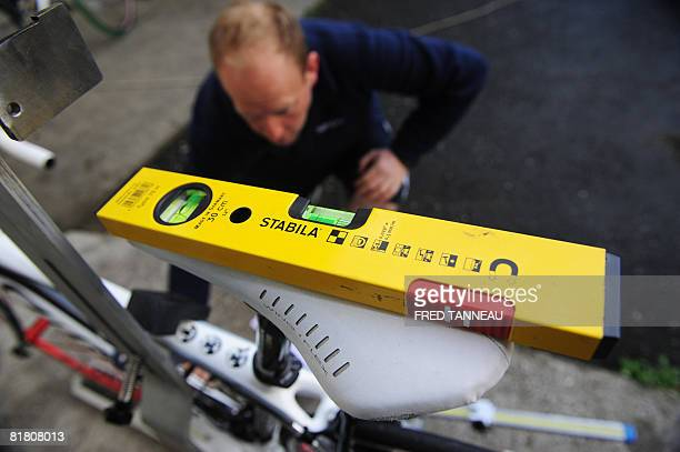 A mechanic checks a team bicycle at the Hostellerie des Enclos hosting the Italian cycling team as a spirit level is put on the saddle of a bicycle...