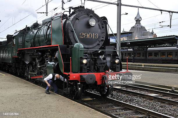 A mechanic checks Belgian 1940s locomotive on April 18 2012 at The Gare du Midi in Brussels on the occasion of the presentation of a cartoon of a...