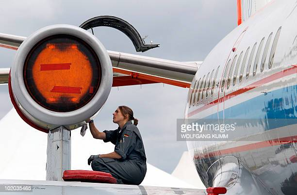 A mechanic checks the engine of a VFW 614 airplane during the International Aerospace Exhibition on June 13 2010 at the Schoenefeld airport in Berlin...