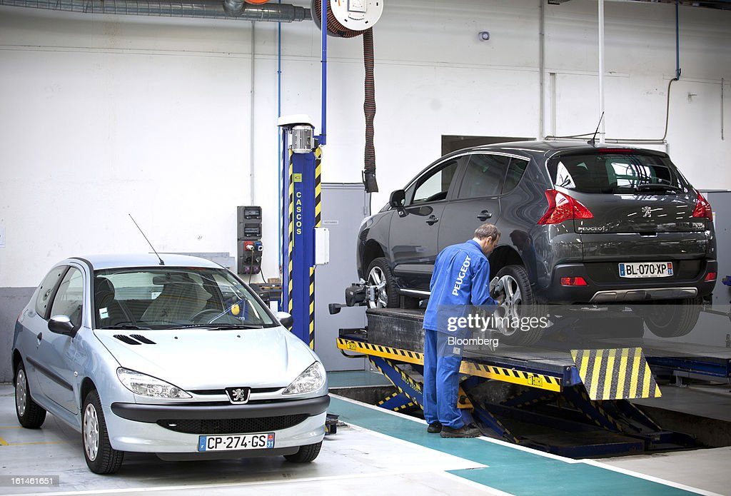 A mechanic checks the rear wheel on a Peugeot 3008 automobile in a service bay at the Peugeot Sial Toulouse dealership in Toulouse, France, on Monday, Feb. 11, 2013. Europe's car market is forecast to drop to 12.3 million vehicles this year, 23 percent below the pre-crisis peak, IHS Automotive research company estimates. Photographer: Balint Porneczi/Bloomberg via Getty Images