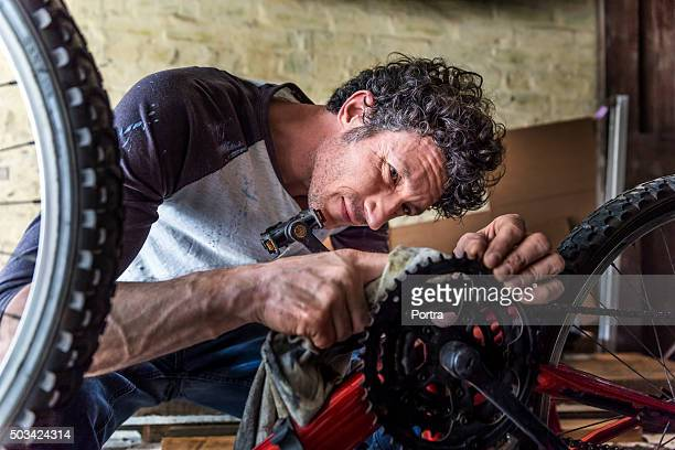 Mechanic cleaning gear of bicycle with cloth