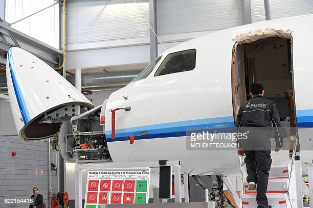 A mechanic climbs into a Falcon 7X aircraft in maintenance inside the Dassault Falcon Service facility next to the cockpit voice recorder and digital...