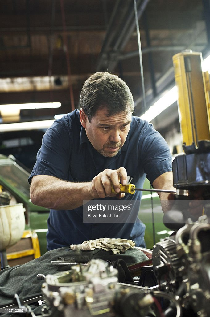 Mechanic concentrates on tightening auto part : Stock Photo