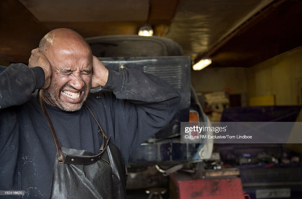 Mechanic covering his ears in garage : Stock Photo