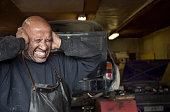 Mechanic covering his ears in garage