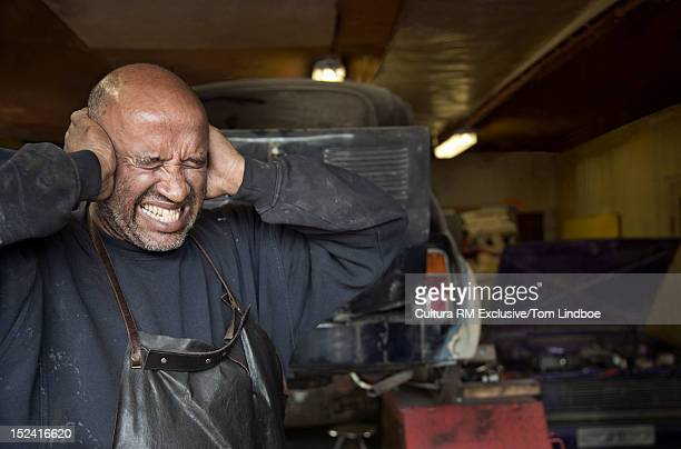 Mechanic covering his ears in garage