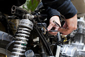 mechanic customizing motorcycle, close-up of hands