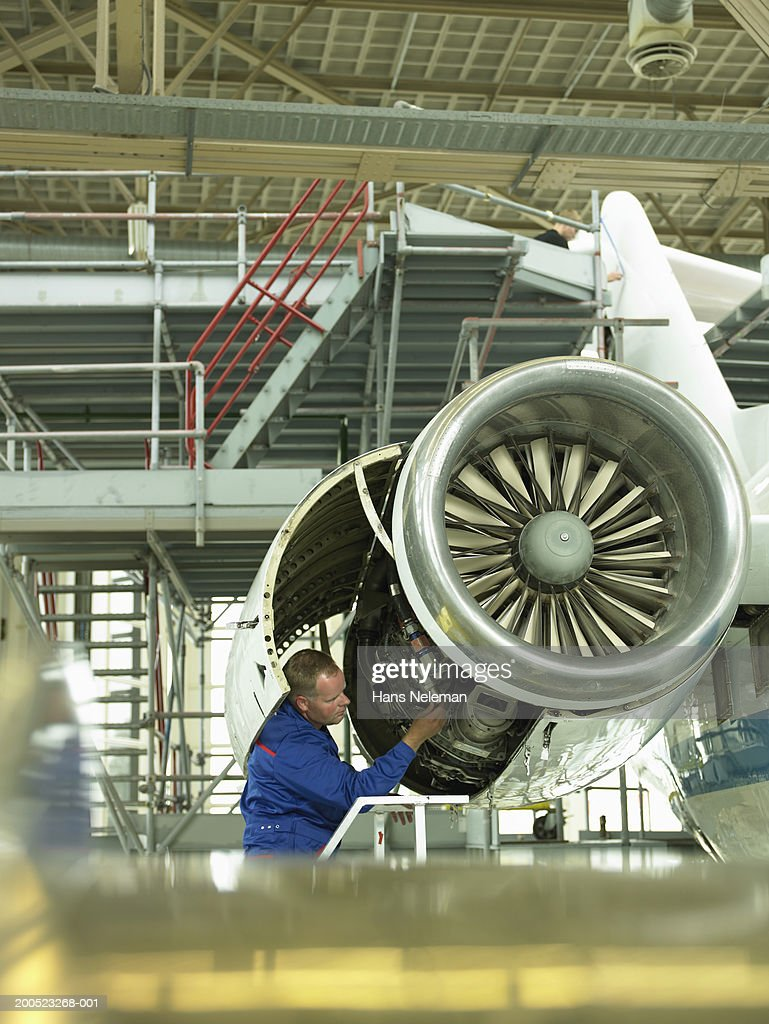 Mechanic examining aircraft in hangar