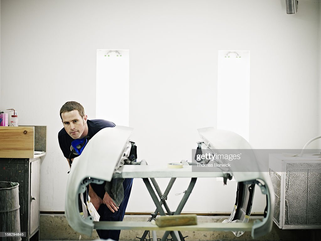 Mechanic examining body work restoration on car : Stock Photo