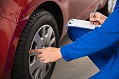 Young Mechanic Writing On Clipboard White Examining Car Wheel