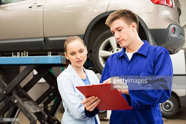 Mechanic Explaining Expenses To Female