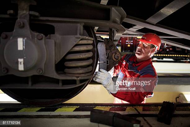 AG mechanic fits a new technology brake pad to a goods wagon at a DB AG workshop during which freight cars are fitted with new composite LL brake...