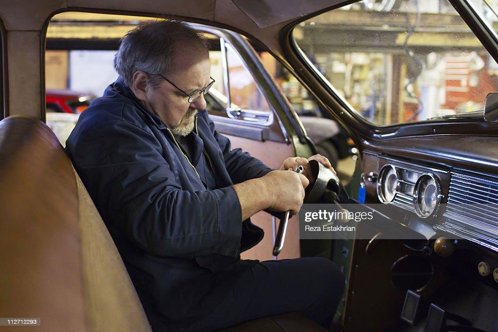 Mechanic fixes steering column in antique auto : Stock Photo