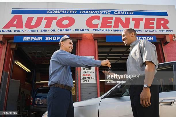 Mechanic giving keys to customer