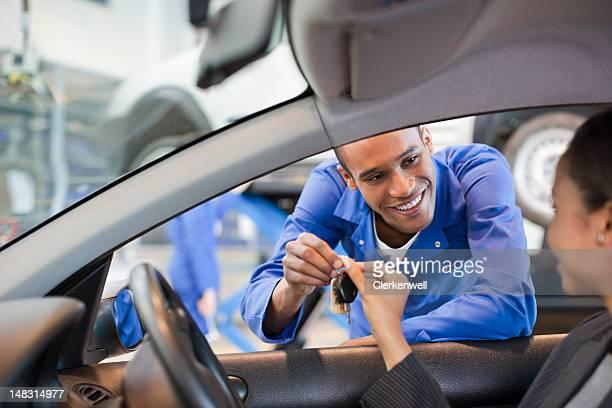 Mechaniker geben Schlüssel, Frau im Auto