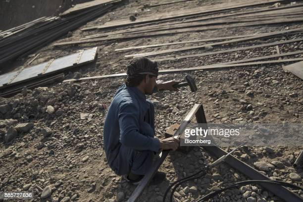 A mechanic hammers metal while building transfer trucks at a yard in Kabul Afghanistan on Saturday Nov 4 2017 The Afghan economy is said to grow 26%...