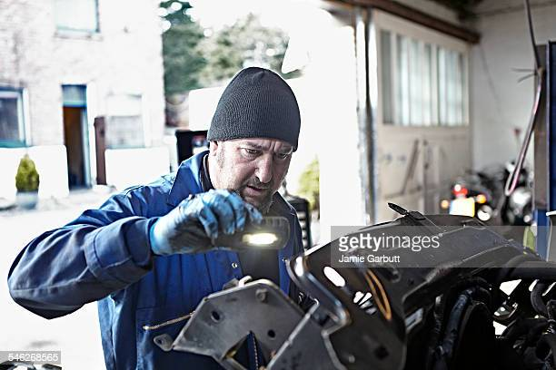 A mechanic hard at work on a engine