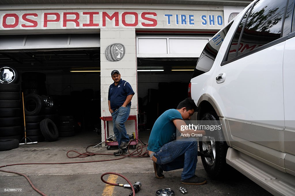 Mechanic Harry Gutierrez, right, puts a tire back on a truck after fixing a flat for customer Rafael Holguin at the Los Primos Tire Shop near Peoria and Colfax June 24, 2016.