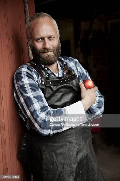 Mechanic holding apple in garage