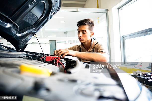 Mechanic in auto repair shop working on car