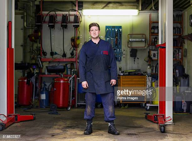 Mechanic in coveralls standing at garage