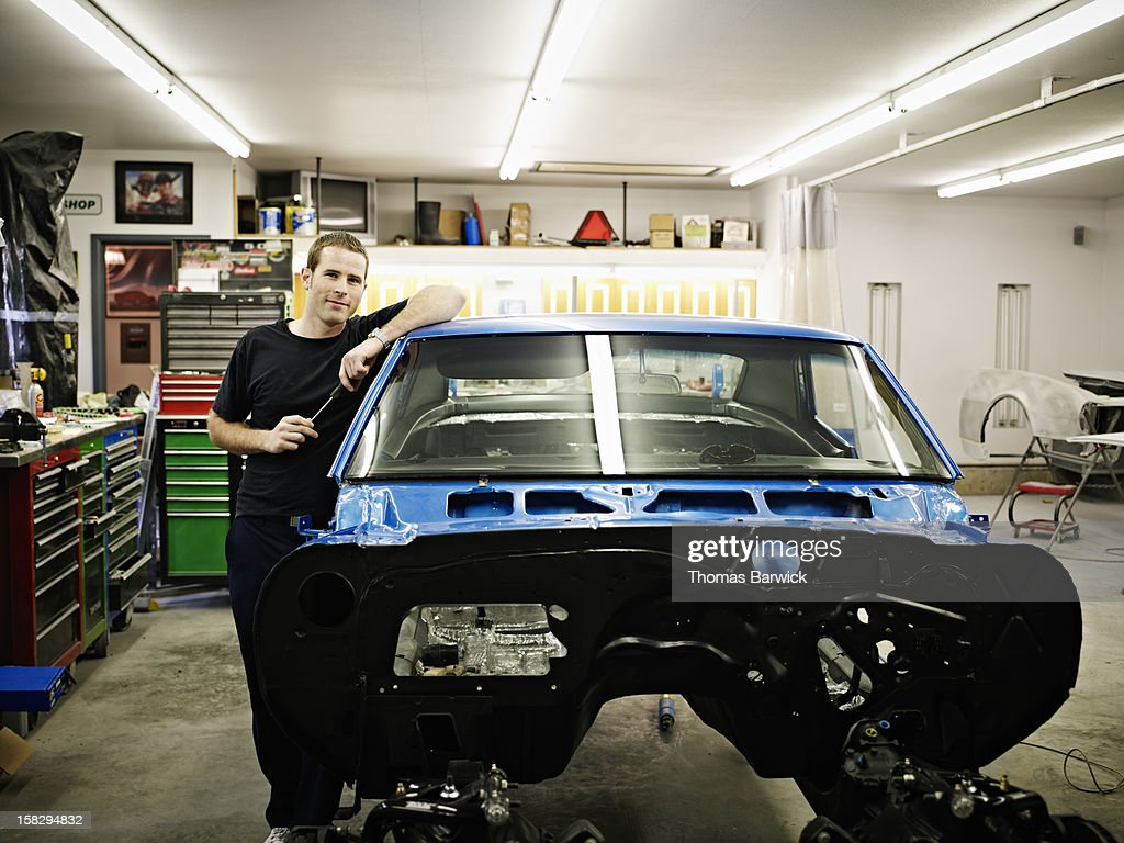 Mechanic in garage with car being restored