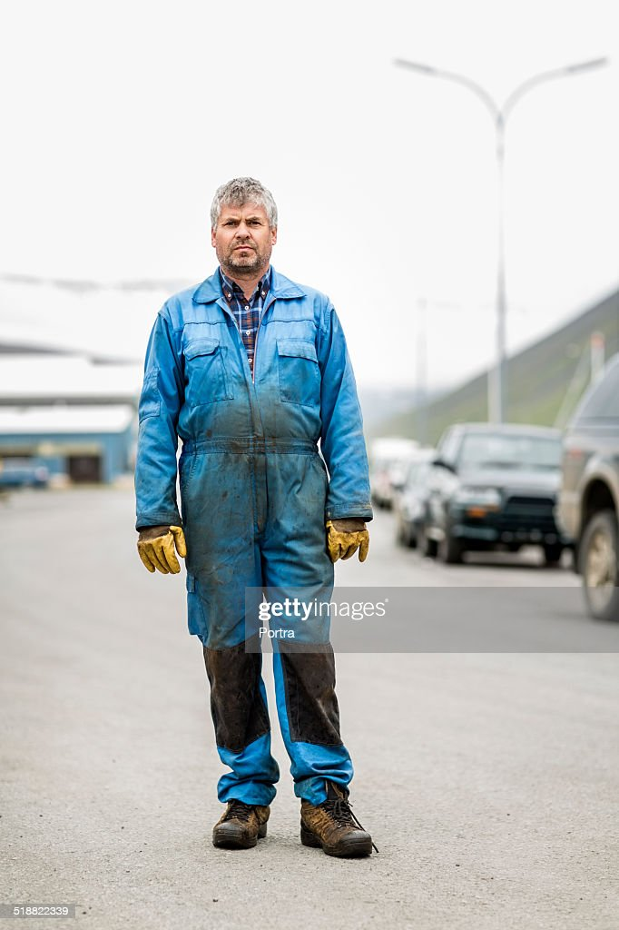 Mechanic in messy coveralls against garage