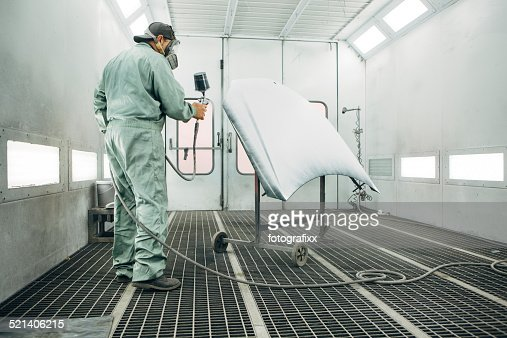 mechanic in Painting Booth spray the hood of a car