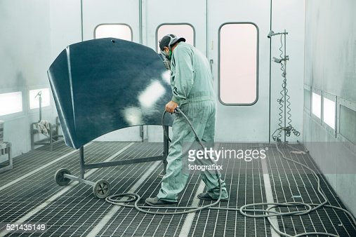 mechanic in painting booth spray the hood of a car stock photo getty. Black Bedroom Furniture Sets. Home Design Ideas