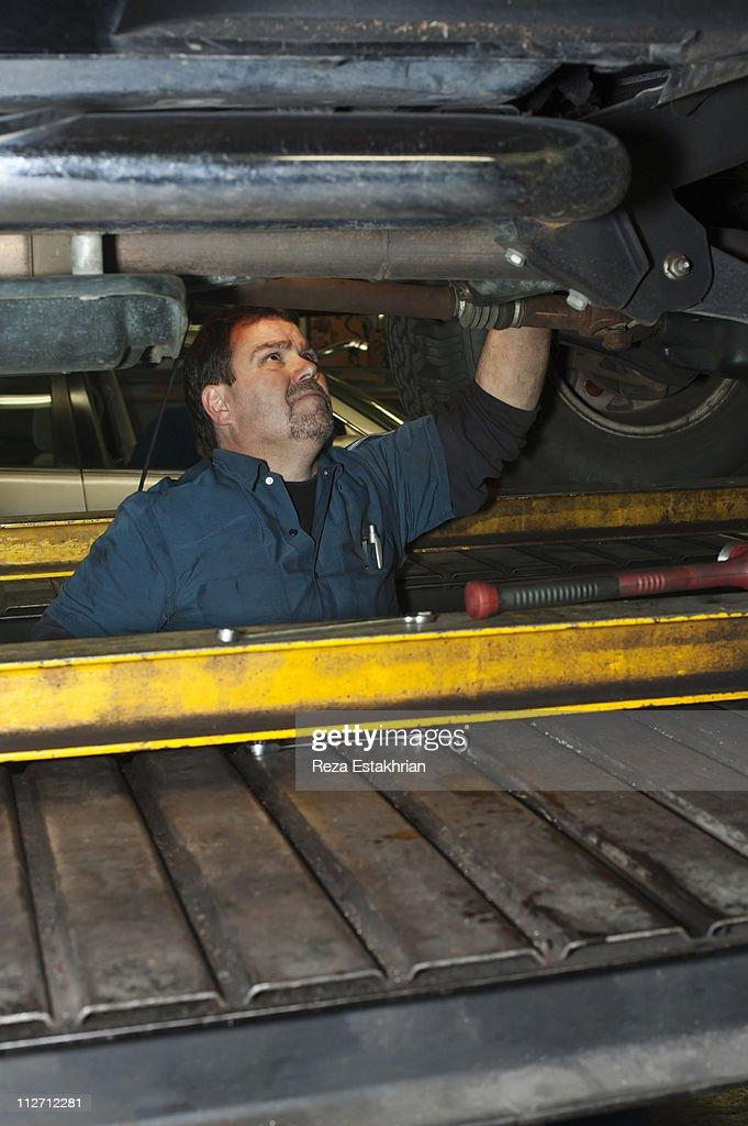 Mechanic investigates under auto : Stock Photo